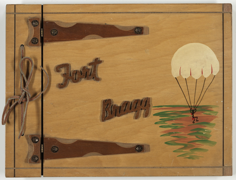 Wooden cover of Albert Lockhart's photographic album decorated with Fort Bragg in raised wooden lettering and a painting of an figure in a descending parachute , 1961