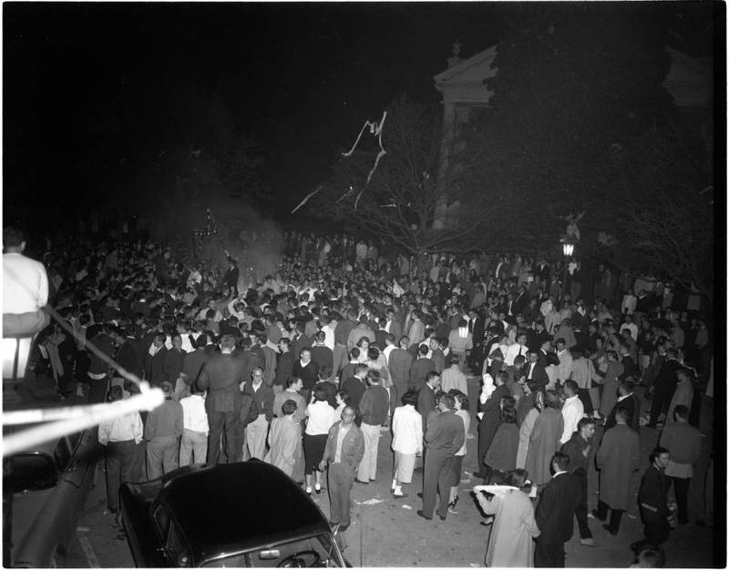 "Crowd scene, including person waving a ""rebel flag,"" during the victory celebration on Franklin Street near campus of the University of North Carolina after the basketball team defeated the University of Kansas for national championship, 23 March 1957."