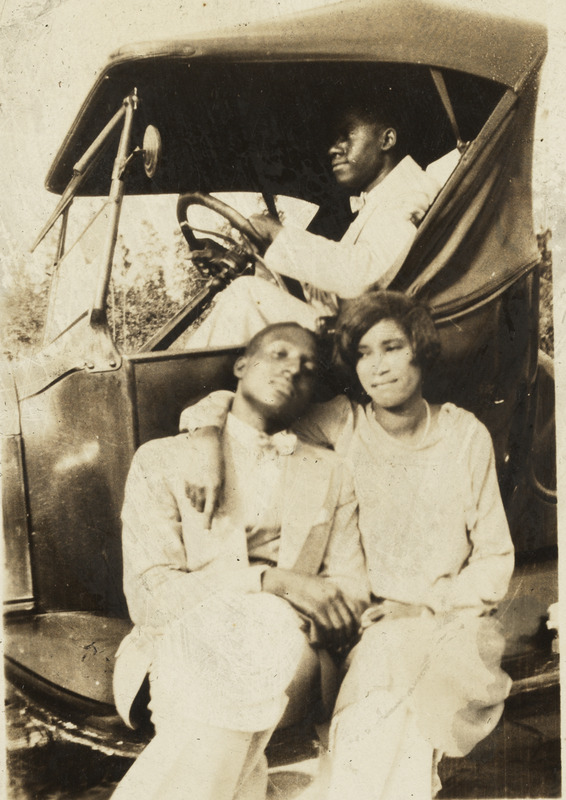 Photograph of a man and woman sitting on the running board of a Ford Model T car