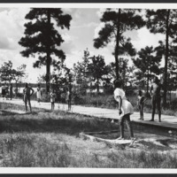 Photo of African American men, women, and children playing horseshoes at Reedy Creek State Park, 1950s