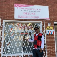 Derrick Green in Front of DeLuxe Barbershop