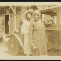 Photograph of two African American women posing in front of a car on a trip to the beach in 1919