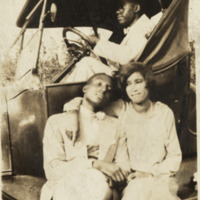 Photograph of a man and woman sitting on the runner board of a car, circa 1941