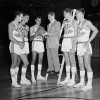 """Tall Team & McGuire"" (identification on mounted photograph). Frank McGuire standing on first step of a step ladder with Pete Brennan, Joe Quigg, Lennie Rosenbluth, Bill Hathaway, and Danny Lotz, members of the 1956-1957 UNC basketball team. Probably October 1956."